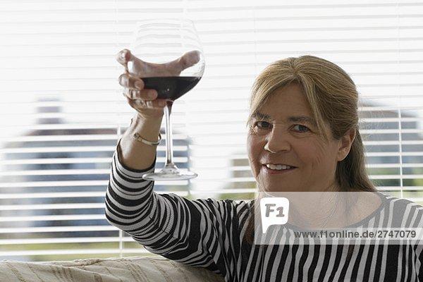 Portrait of ältere Frau Rösten mit einem Glas Wein