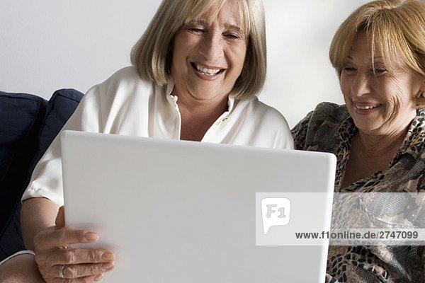 Zwei senior DAMENLAUF Blick auf einem laptop
