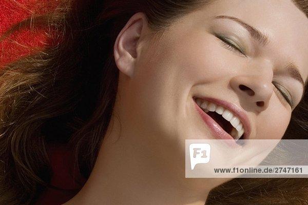 Nahaufnahme einer jungen Frau lächelnd mit ihren Augen geschlossen