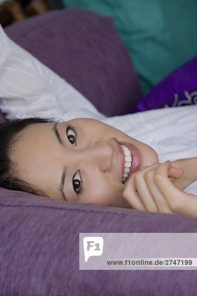 Portrait einer jungen Frau hinlegen und lächelnd