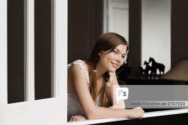 Frau stützte sich auf ein Fenster und lächelnd