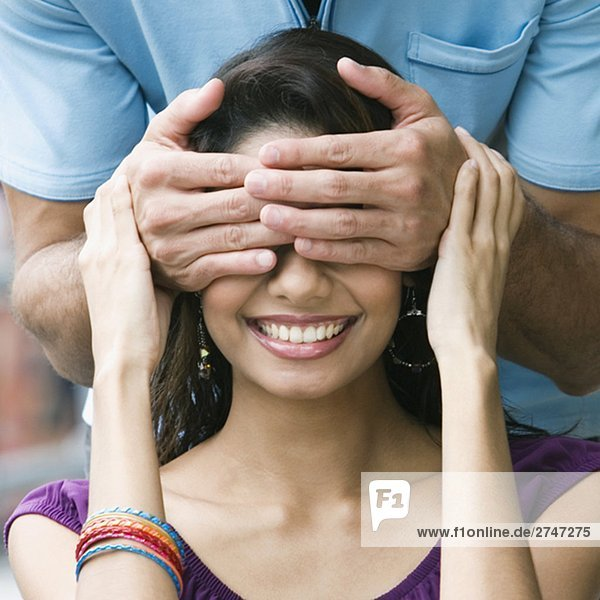 Mid section view of a mid adult man covering eyes of a young woman with his hands
