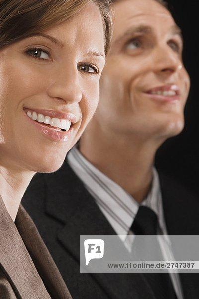 Porträt von geschäftsfrau mit einem Geschäftsmann hinter ihr