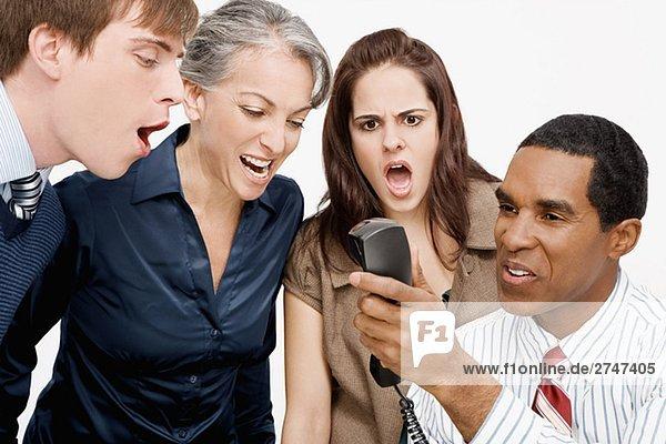 Unternehmer ein Telefon mit drei Geschäftsleute Geschrei hält