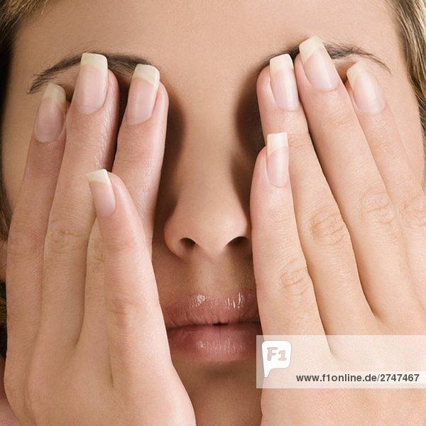 Nahaufnahme einer jungen Frau  die ihre Augen mit den Händen