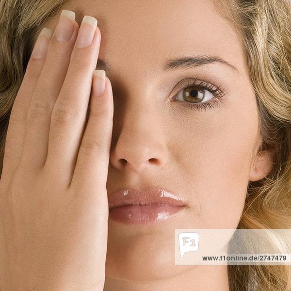 Nahaufnahme einer jungen Frau mit ihrem ein Auge