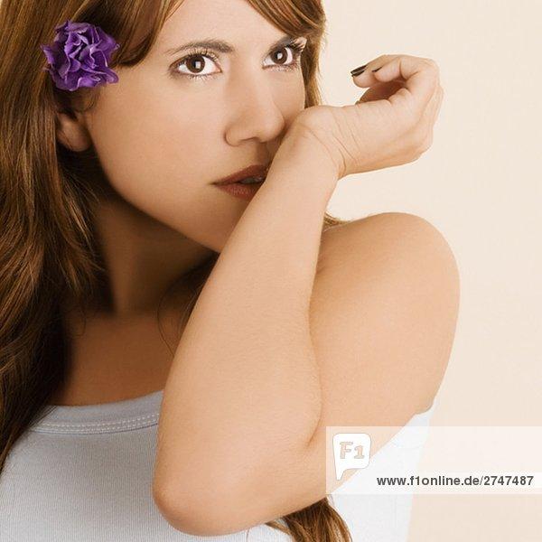 Nahaufnahme einer jungen Frau mit einer Blume im Haar