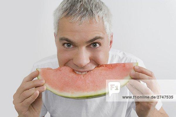 Porträt von ein älterer Mann Essen ein Stück der Wassermelone