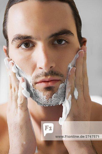 Porträt eines jungen Mannes Rasiercreme auf seinem Gesicht anwenden