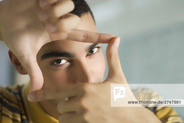 Porträt eines jungen Mannes machen einen Finger-frame