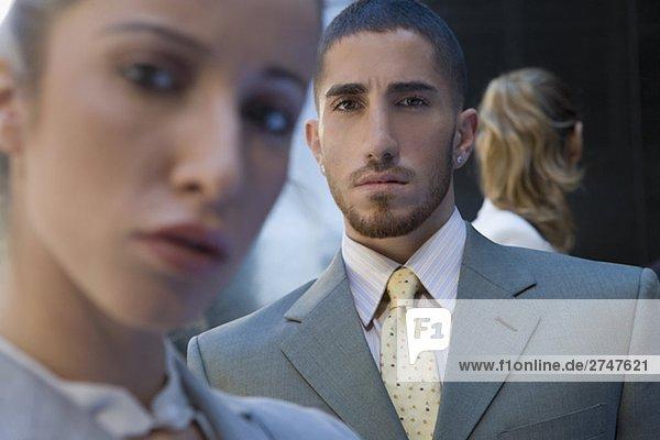 Portrait eines Kaufmanns zwischen zwei Geschäftsfrauen