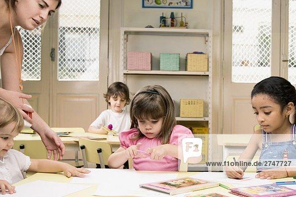 Weibliche Lehrer ihren Schülern in einem Klassenzimmer