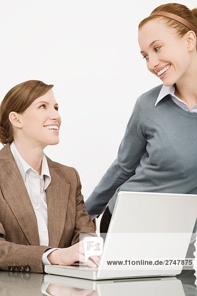 Two businesswomen smiling at each other