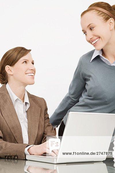 Zwei Geschäftsfrauen lächelnd einander
