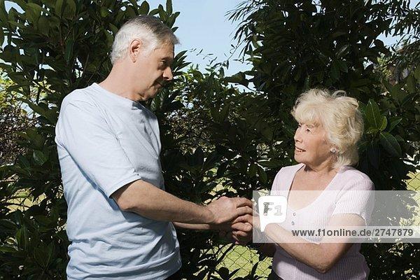 Senioren halten einander Hände in einem Garten