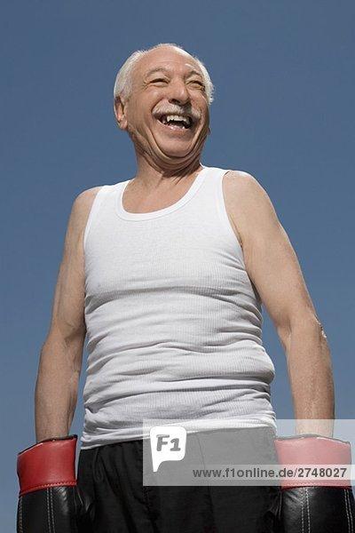 älterer Mann tragen Boxhandschuhe und lächelnd