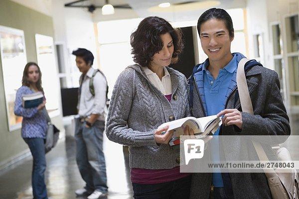 Porträt eines jungen Mannes mit einer jungen Frau hält Bücher und lächelnd ständigen