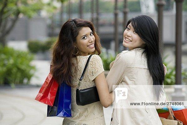Portrait von zwei jungen Frauen tragen Tragetaschen und lächelnd