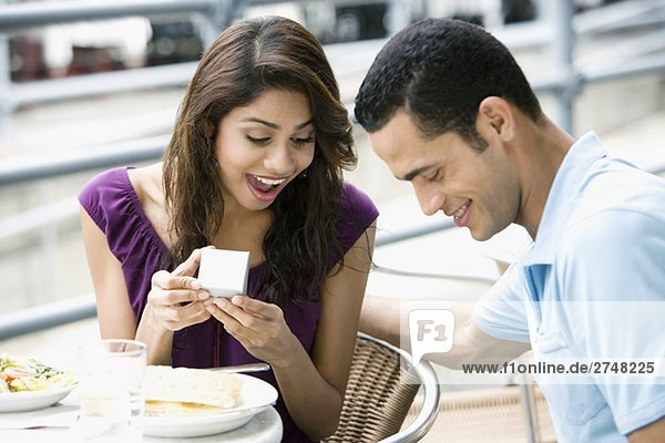 Couple sitting at a sidewalk cafe and smiling
