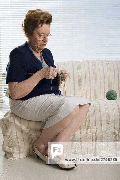 ältere Frau auf einer Couch sitzen und stricken