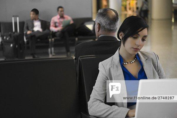 Geschäftsfrau mit einem Laptop mit einem Geschäftsmann hinter ihm auf einem Flughafen