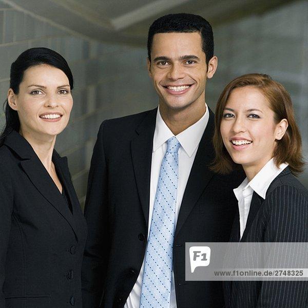 Kaufmann und zwei Geschäftsfrauen stehen zusammen und lächelnd