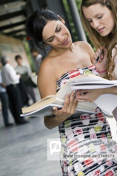 Zwei junge Frauen betrachten ein Buch