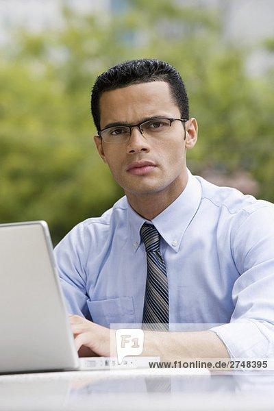 Portrait eines Kaufmanns mit einem Laptop in einem Bürgersteig Café