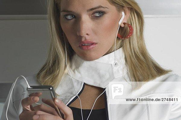 Nahaufnahme einer jungen Frau einen MP3-Player anhören