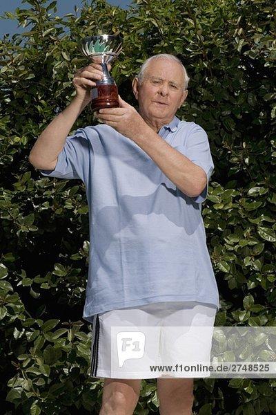 älterer Mann  hält eine Trophäe