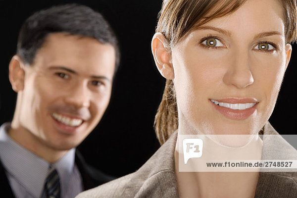 Porträt von lächelnd mit einem Geschäftsmann hinter ihr geschäftsfrau