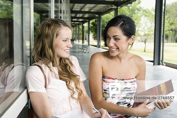 Nahaufnahme der zwei jungen Frauen sitzen in einem Korridor und lächelnd