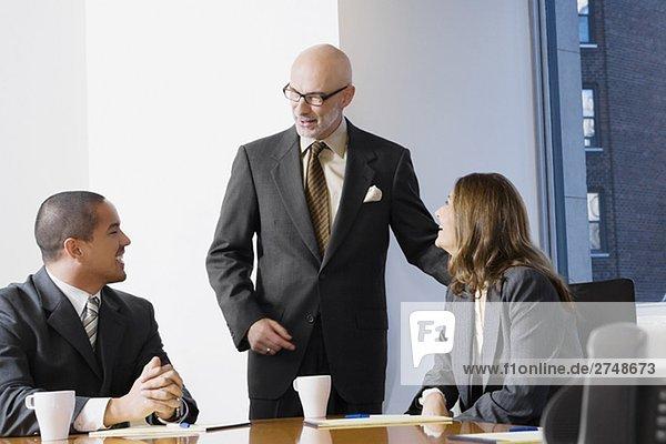 Geschäftsleute in einem Sitzungssaal diskutieren