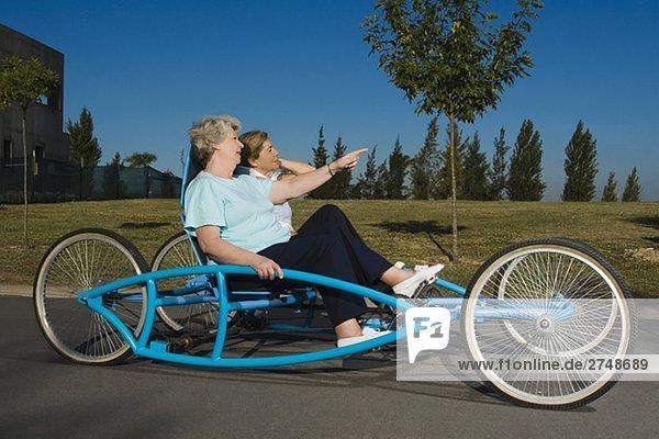 Zwei senior DAMENLAUF Reiten ein quadracycle