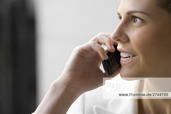 Nahaufnahme einer jungen Frau Gespräch auf einem Mobiltelefon und lächelnd