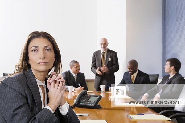 Porträt von geschäftsfrau mit anderen Führungskräften in einem Sitzungssaal