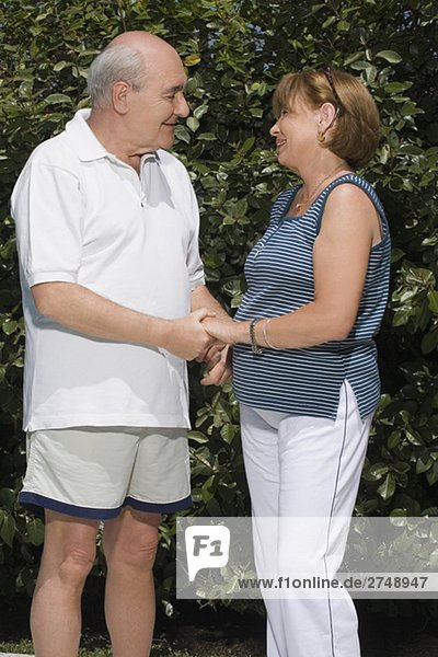 Senior couple holding each other hands in a garden