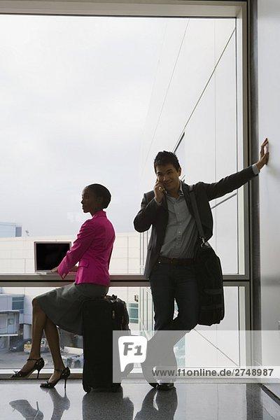 Gespräch auf einem Mobiltelefon mit mit einem Laptop neben ihm geschäftsfrau kaufmann