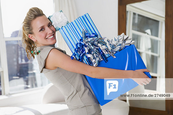 Portrait of a young woman holding a stack of gifts and smiling