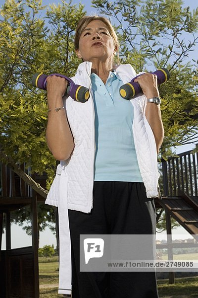 Low angle view of a senior woman exercising with dumbbells