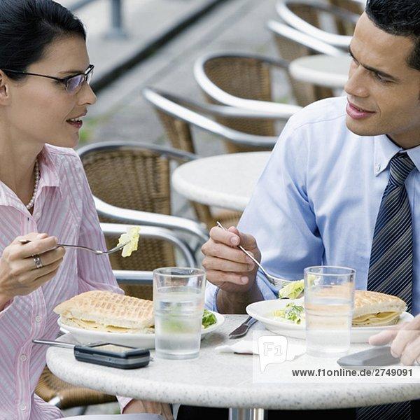 Kaufmann und eine geschäftsfrau mit Mittagessen in einem Bürgersteig Café
