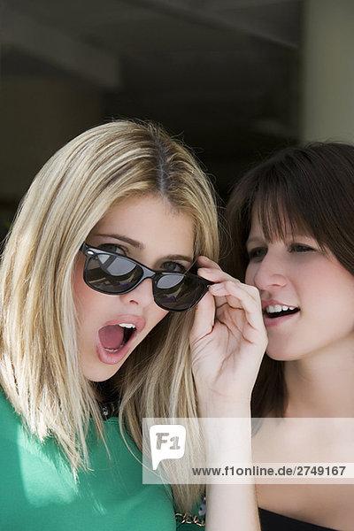 Nahaufnahme einer jungen Frau mit einer anderen jungen Frau lächelnd neben ihr überrascht suchen