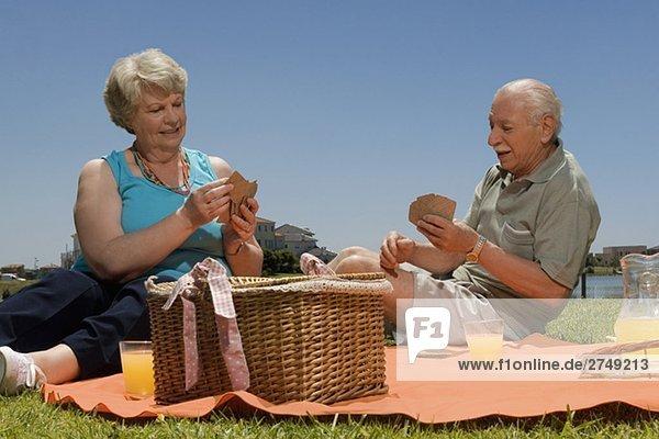 älteres Paar Spielkarten bei Picknick