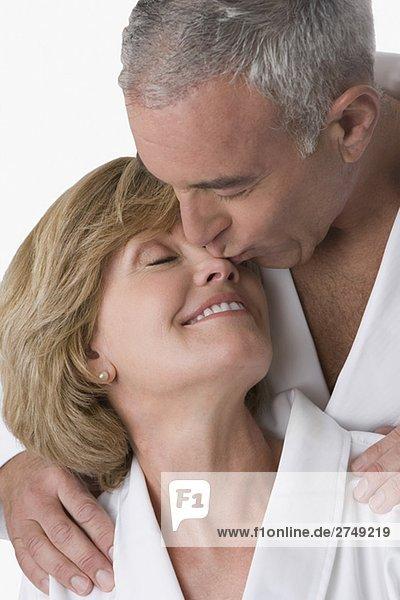 Nahaufnahme von einem älterer Mann küssen eine reife Frau Nase