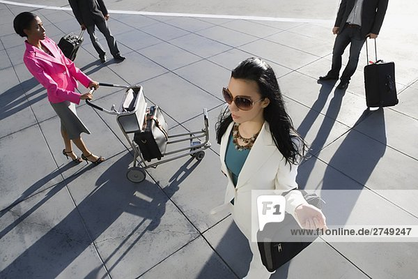 High angle view of two businesswomen and two businessmen walking at an airport