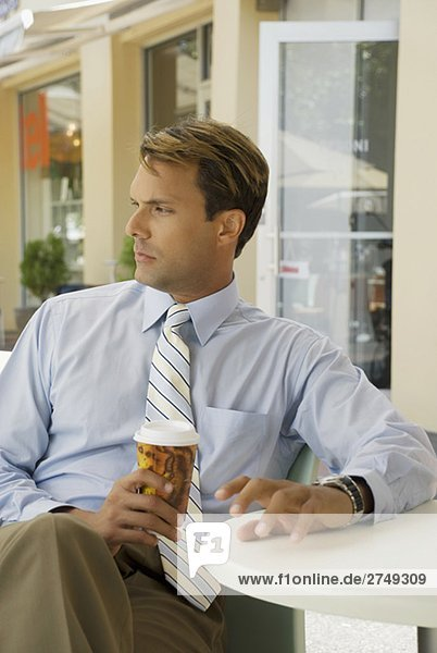 Businessman sitting in a restaurant and holding a disposable cup