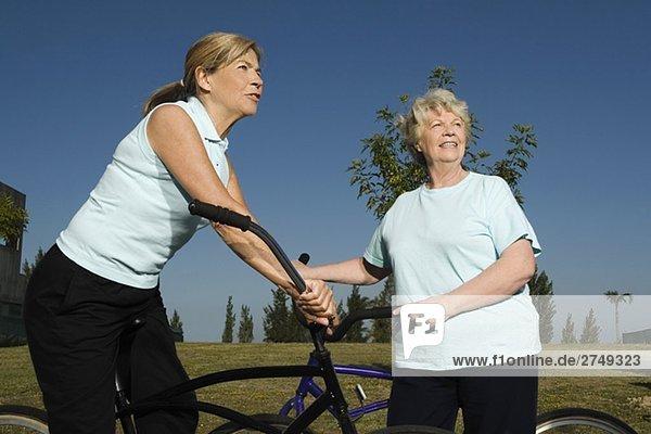 Zwei senior DAMENLAUF stehend mit Fahrrädern