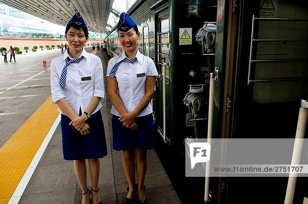Ziemlich mongolischen Zug Personel Stand in der Nähe der mongolischen Trans-Zug in Peking-Bahnhof