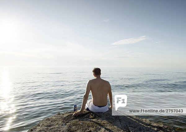 Man sitting on rock by the sea
