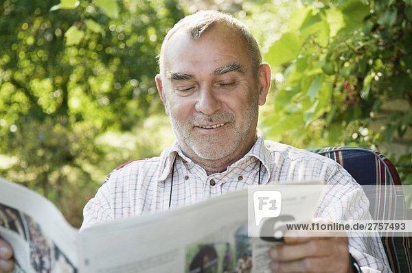 Smiling man reading newspaper Smiling man reading newspaper